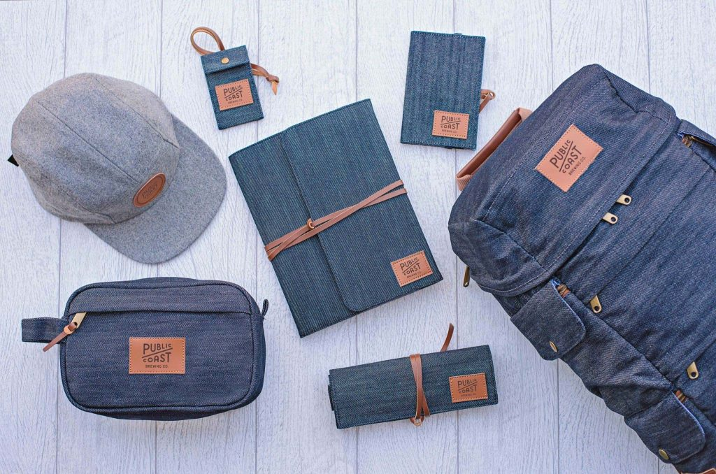 Image of custom branded hat, dopp kit, luggage tag, journal, tech organizer, and backpack.